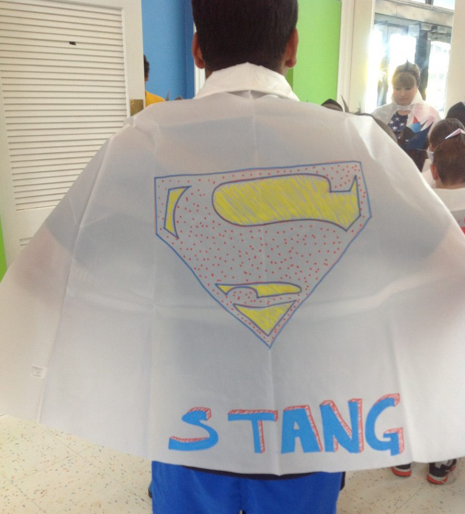 summer camp activity with superhero capes