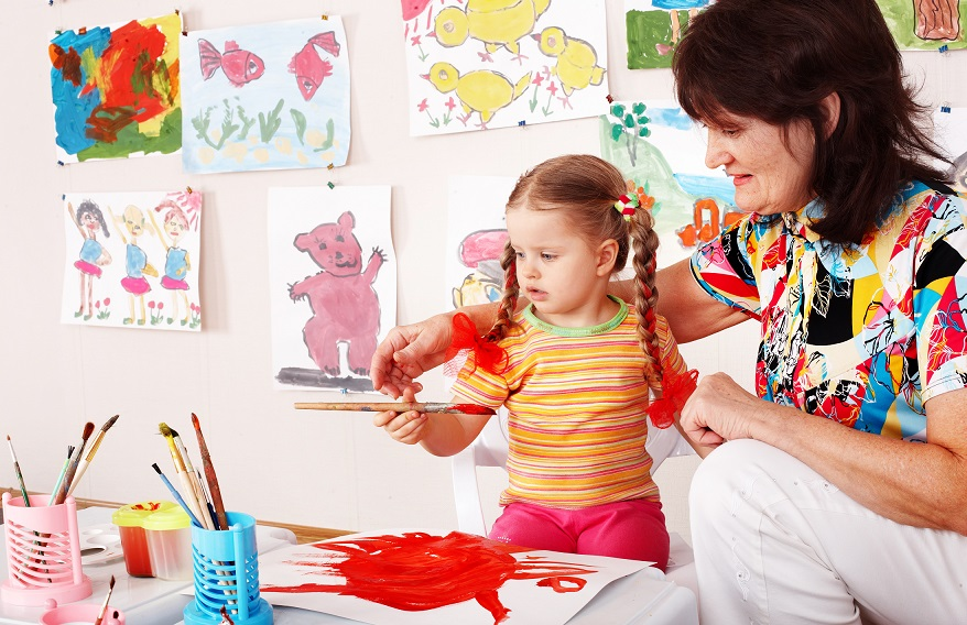 Child with teacher draw paints in play room. Prescooler.